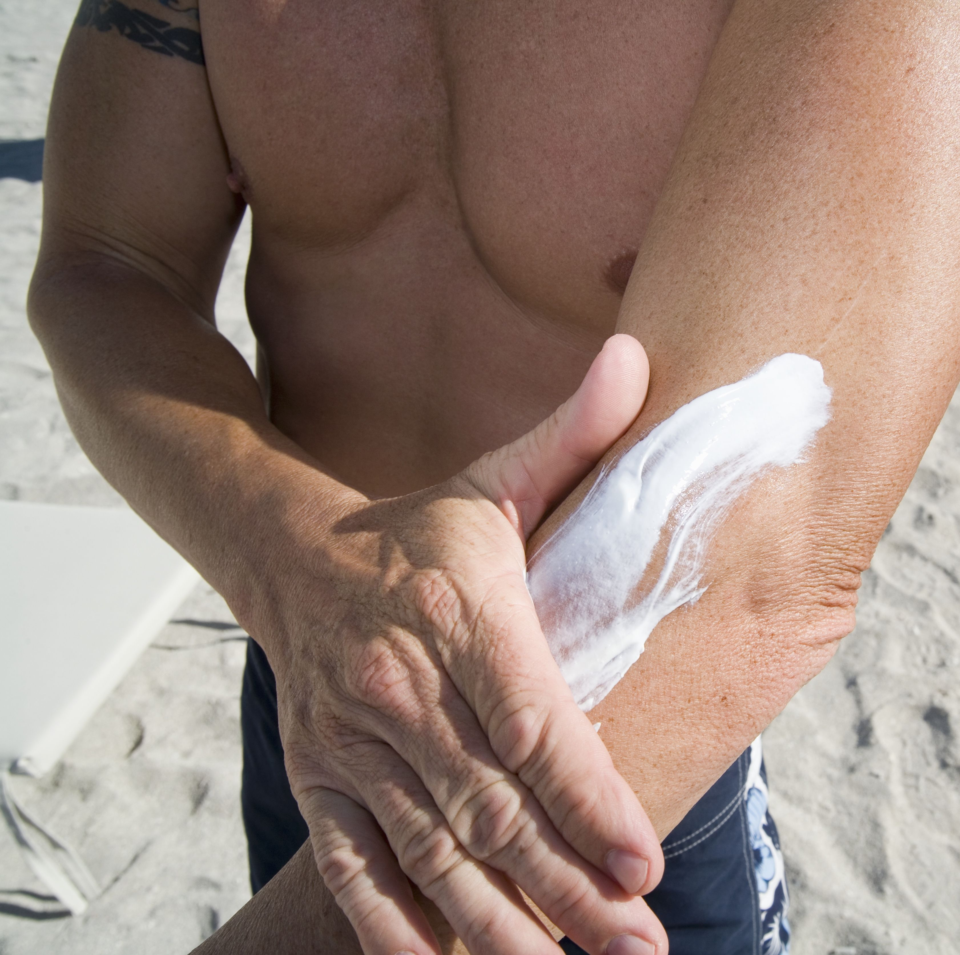 Man standing on beach and applying sun cream to arm