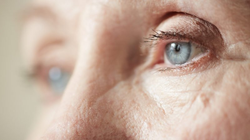 Sad blue-grey eyes of elderly woman looking to the side, extreme close-up shot