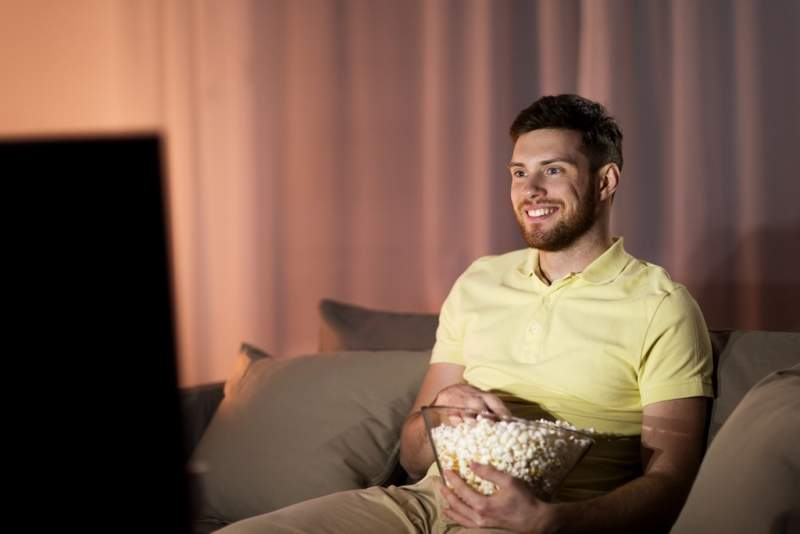 happy-man-with-popcorn-watching-tv-at-night