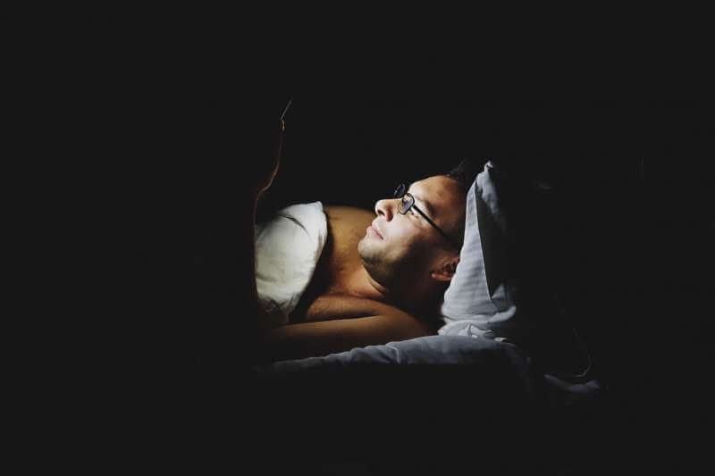 man-using-mobile-device-in-bed-before-sleep
