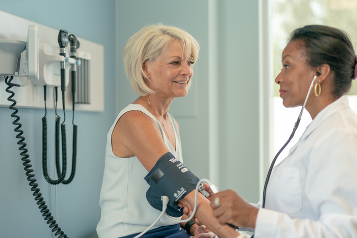 A woman having her blood pressure checked by a doctor at a routine examination.