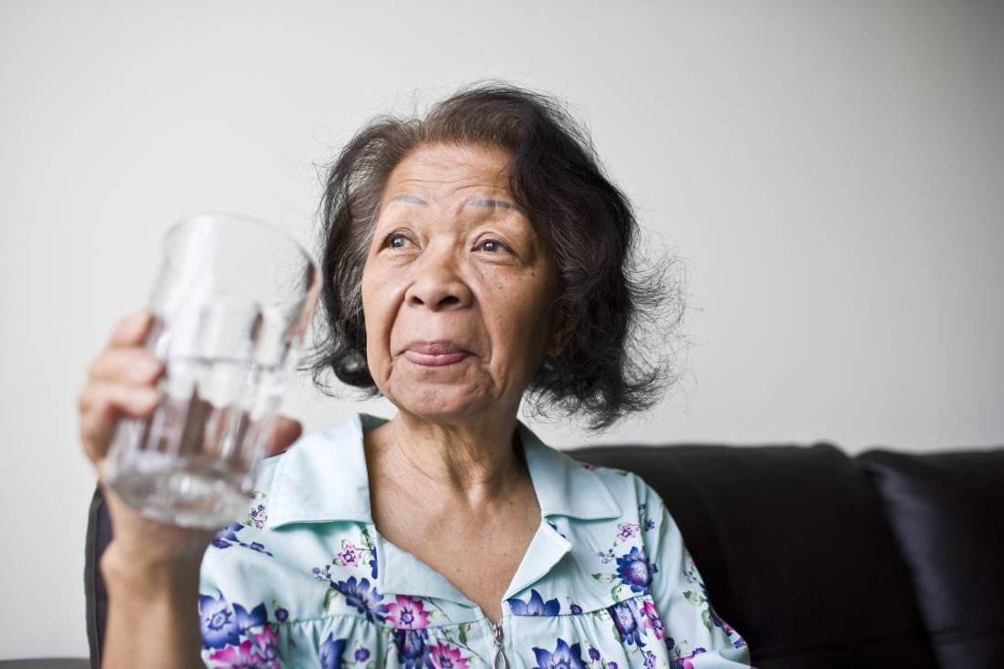 senior woman holding glass of water