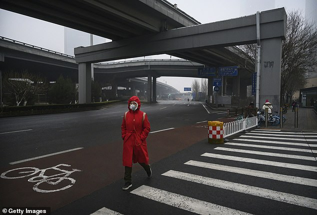 A woman wearing a full-body coat and a protective mask is seen walking on a deserted road in Beijing as the country is gripped by fear of the coronavirus spreading