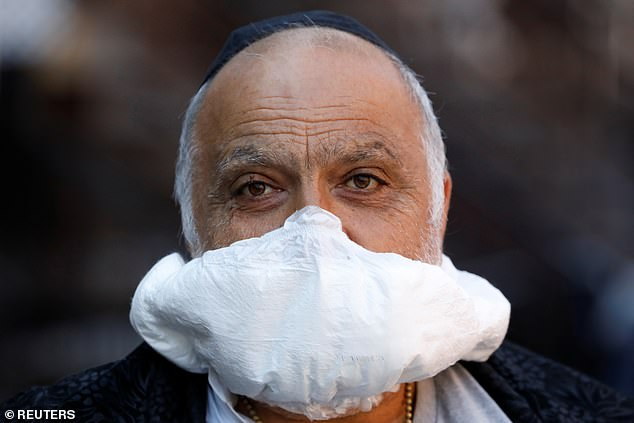 A man is seen using a nappy as a makeshift face mask in Brooklyn, New York City