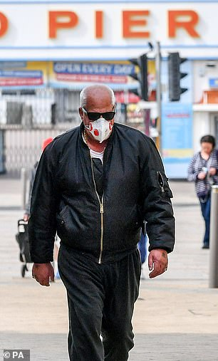 A man wearing a respirator face mask walks along Weston-super-Mare on Easter Sunday