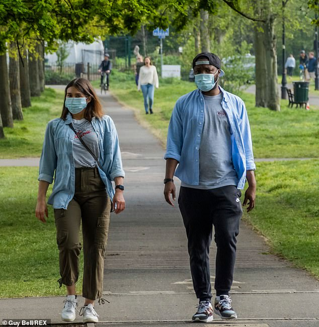 Two people are pictured wearing masks on London's Clapham Common on Sunday. Ministers could make a decision this week on whether to order the use of protective equipment for millions of Britons in the workplace and on public transport