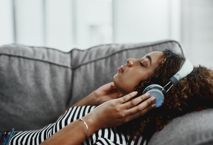 Woman lying down and listening to soothing music