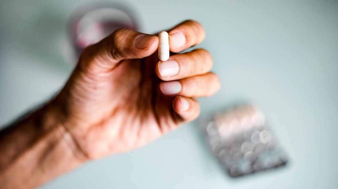 a man holding a zinc tablet that he is going to take as a home remedy for premature ejaculation