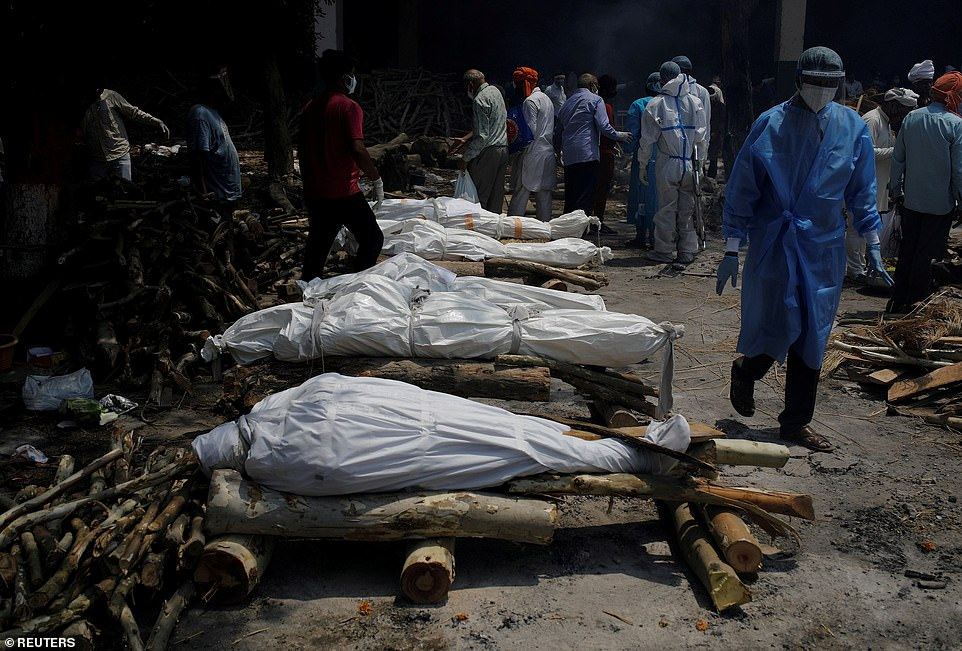 A health worker wearing personal protective equipment (PPE) walks past the funeral pyres of those who died from the coronavirus disease (COVID-19) during a mass cremation at a crematorium in New Delhi, India, April 26