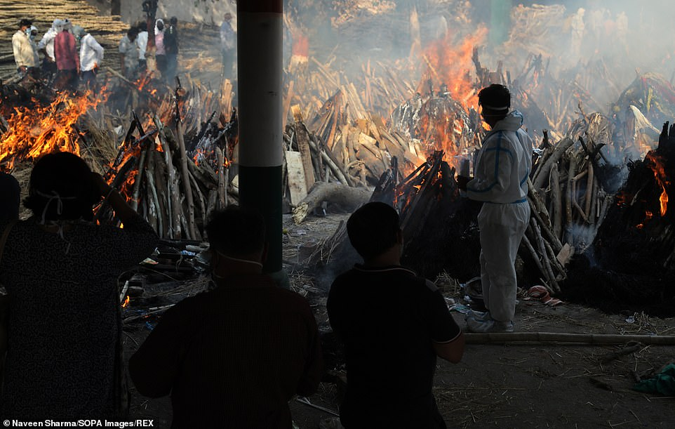Family members look on as several funeral pyres of those patients who died of COVID-19 disease burn up during the mass cremation at Ghazipur cremation ground in New Delhi