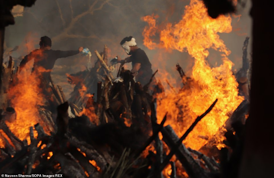 Cremation ground workers in New Delhi, India, tend to pyres that are used to burn the bodies of Covid victims