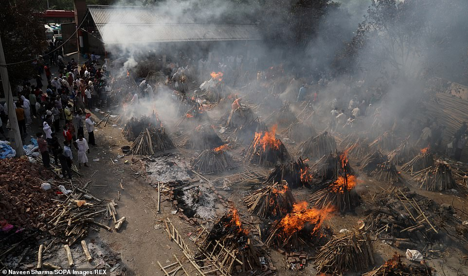 Family members perform last funeral rites for their relatives who died from the COVID-19 disease before cremation at Ghazipur cremation ground in New Delhi