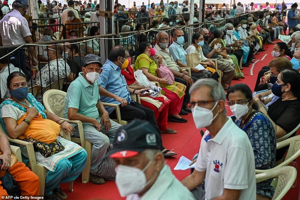People queue up to receive a dose of a Covid-19 coronavirus vaccine at a vaccination centre in Mumbai