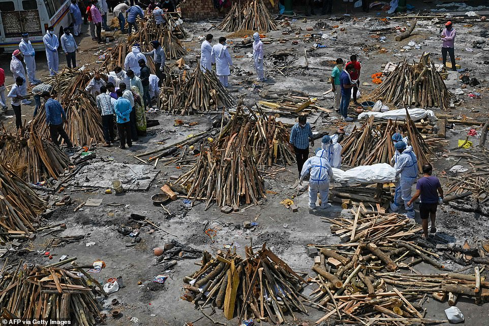 Crematorium workers pile wood on top of bodies for burning at a cremation ground in New Delhi