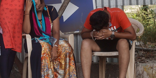 May 3, 2021: Relatives of a person who died of COVID-19 mourn outside a field hospital in Mumbai, India.